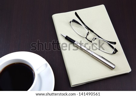 notebook with coffee cup on table