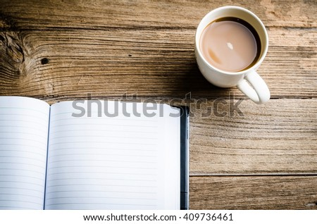 notebook with coffee cup on wooden background