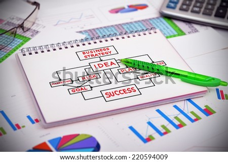 notebook with drawing business plan and financial charts - stock photo