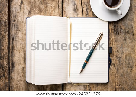 Notebook with elegant fountain pen and cup of espresso. Top view of writer's workplace  - stock photo
