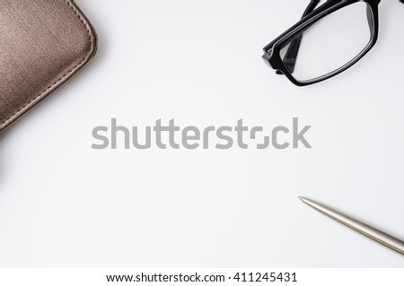 Notebook with leather cover, silver ballpoint pen and glassess on white background. Copy space in the center from top view - stock photo