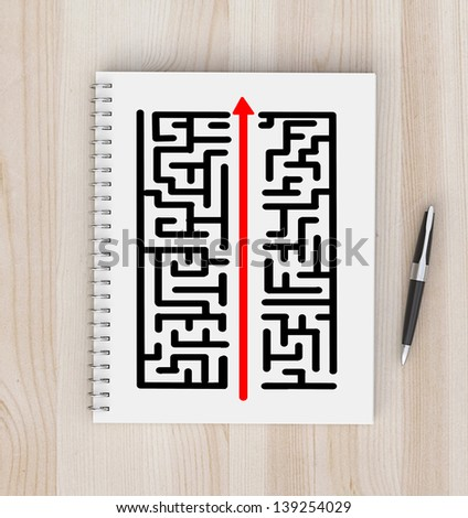 notebook with maze and pen