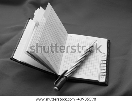 notebook with pen - black and white - stock photo