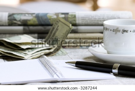 Notebook with pen, money, newspapers and cup of coffee - stock photo