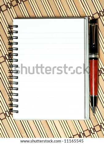 notebook with pen on bamboo mat - stock photo
