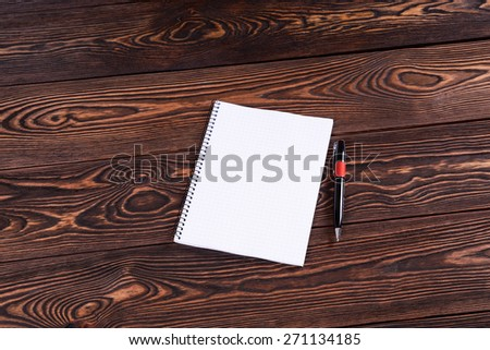 Notebook with pen on brown table - stock photo