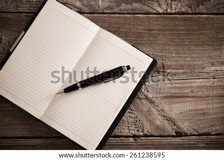 notebook with pen  on old  wooden table - stock photo