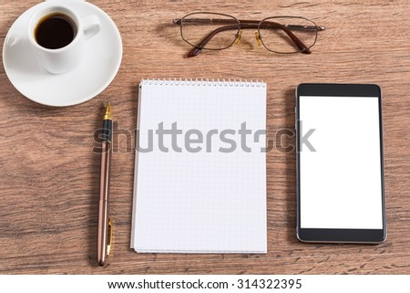 Notebook with pen, smart phone and coffee cup on wooden table - stock photo