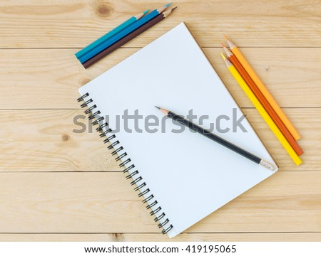 Notebook with pencil and color pencil on wooden table. - stock photo