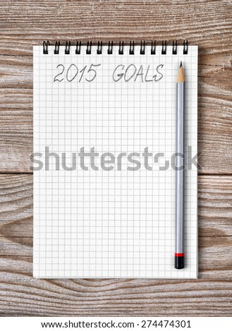 Notebook with pencil and goals of year 2015 on wooden background