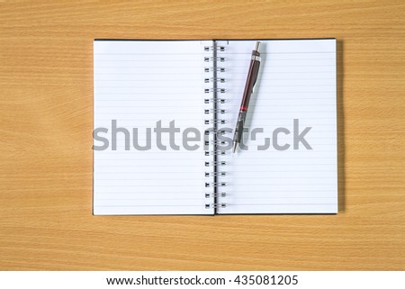 Notebook with pencil on wooden background