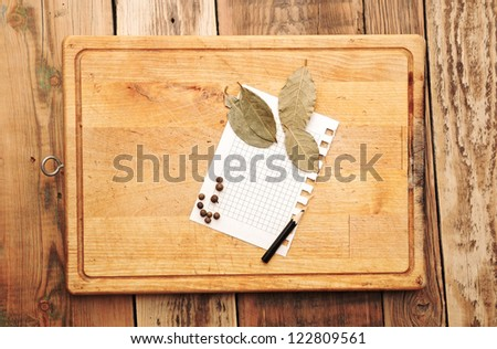 notebook with pencil to write recipes on the background of a cutting board with spices