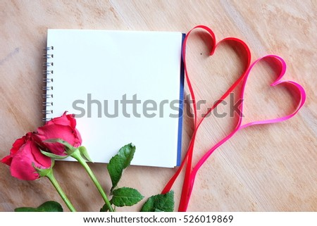 Notebook with rose on wooden background