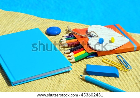 Notebook with school supplies on a pool background.