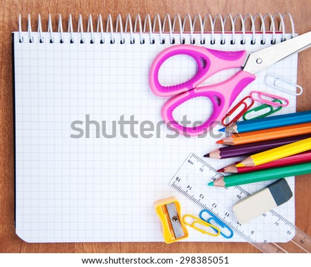 notebook with school supplies on a wooden background - stock photo