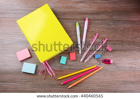 Notebook with stationery on wooden background - stock photo