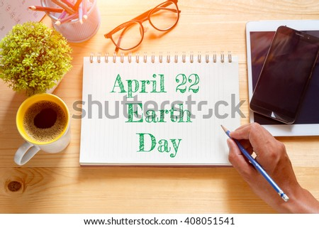 """Notebook with text inside"""" April 22 Earth Day """" on table with coffee. Concept  Earth Day - stock photo"""
