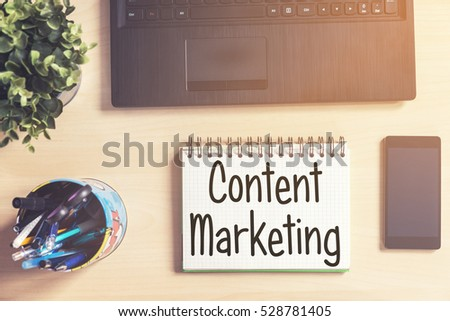 Notebook with text inside Content Marketing on table with laptop, mobile phone and plant
