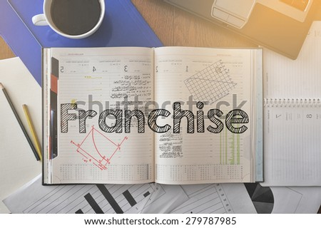 Notebook with text inside Franchise on table with coffee, some diagrams on paper and laptop  - stock photo