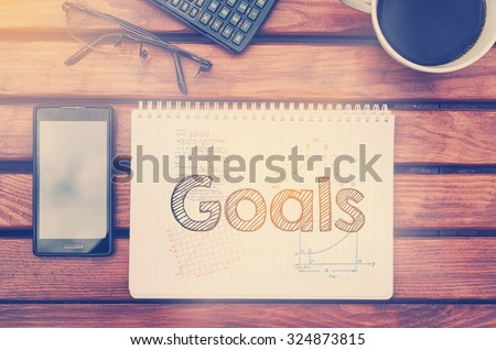 Notebook with text inside Goals on table with coffee, mobile phone and glasses.  - stock photo