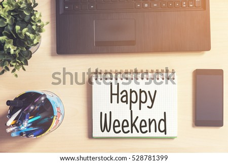 Notebook with text inside Happy Weekend on table with laptop, mobile phone and plant