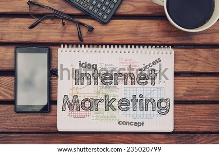 Notebook with text inside Internet Marketing on table with coffee, mobile phone and glasses.  - stock photo