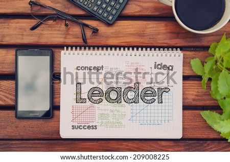 Notebook with text inside leader on table with coffee, mobile phone and glasses.  - stock photo