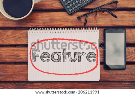 Notebook with text inside  on table with coffee, mobile phone and glasses.  - stock photo
