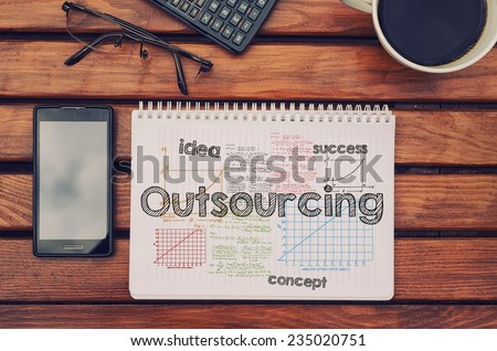 Notebook with text inside Outsourcing on table with coffee, mobile phone and glasses.  - stock photo