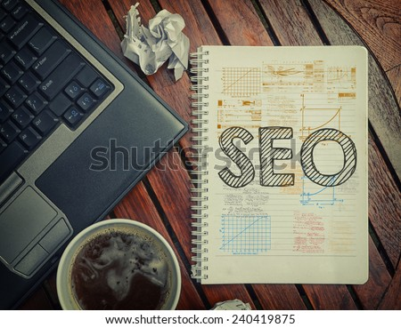Notebook with text inside SEO on table with coffee, laptop pc and crumpled sheets - stock photo