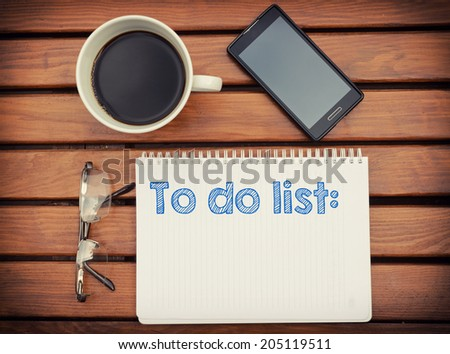 Notebook with text inside To do list on table with coffee, mobile phone and glasses. - stock photo
