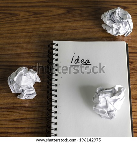 notebook write idea word with crumpled on wooden background - stock photo