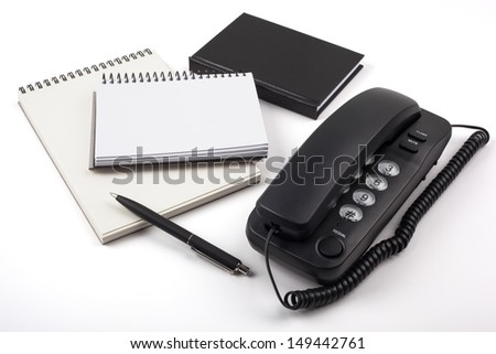 Notebooks, a ballpoint pen and a black phone on white background. - stock photo