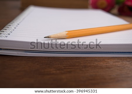 Notebooks and pensil on wooden background, camelia