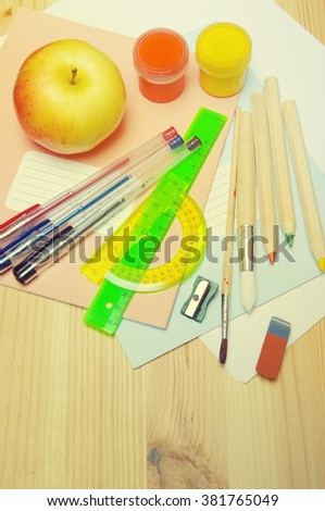 Notebooks, brush, colored pencils, pen, ruler, sharpener, eraser, apple on a wooden surface. School supplies for drawing and the letter - stock photo