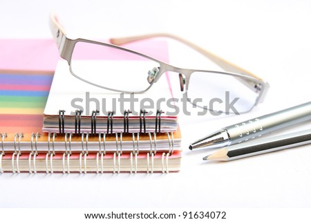 notebooks pen and glasses on white