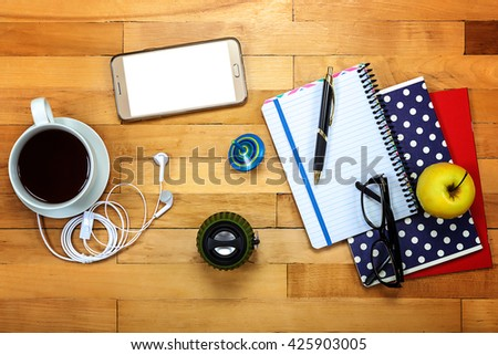 Notebooks, pen, glasses, music speakers, headphones, mobile phone, cup of tea, apple on a wooden background. - stock photo