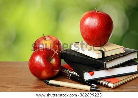 Notebooks, pens and apples on a table with green bokeh background - stock photo