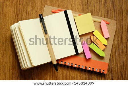 Notebooks, pens and stickers on wooden background - stock photo