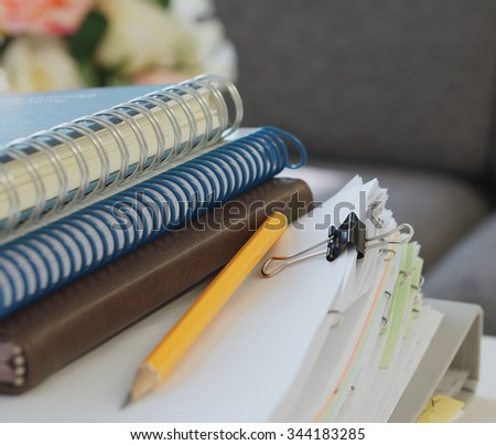 Notebooks, yellow pencil, stack of document and file placed on desk at office. - stock photo