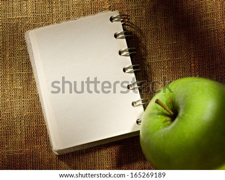 Notepad and apple on the sacking background
