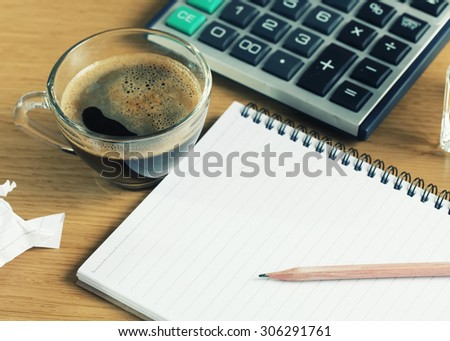 Notepad and coffee cup on table in office.