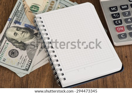 Notepad and heap of dollars With Copy Space - stock photo