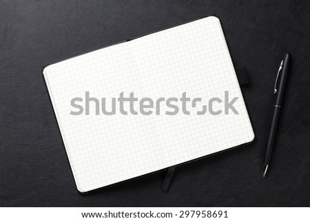 Notepad and pen on office leather desk. Top view with copy space - stock photo