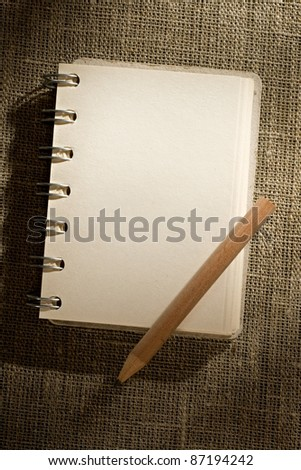 Notepad and pencil isolated on the sacking background