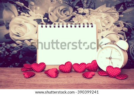 notepad and small heart with blur bunch of fabric roses background - stock photo
