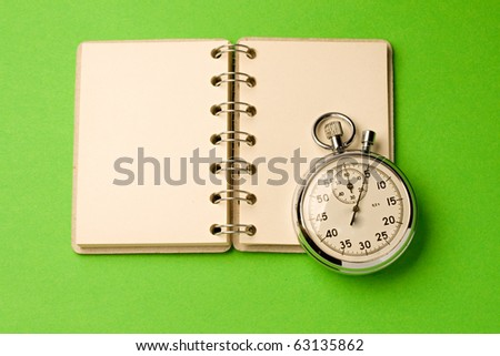 Notepad and stopwatch isolated on green background