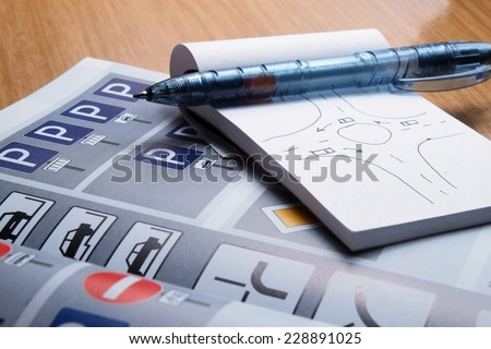 Notepad, book of traffic rules and pen on a desk table. Studying and preparing for driving test exam - stock photo