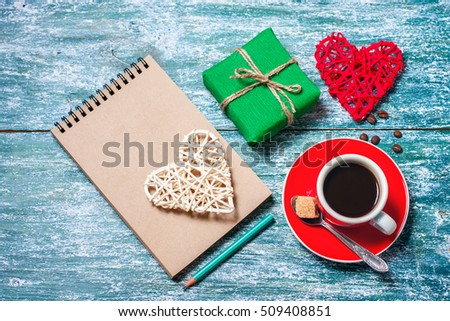 Notepad, cup of coffee, box with gift on a blue wooden table. Space for text, top view