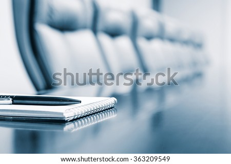 Notepad for agenda kept on table in empty corporate conference room before business meeting in blue tone - stock photo